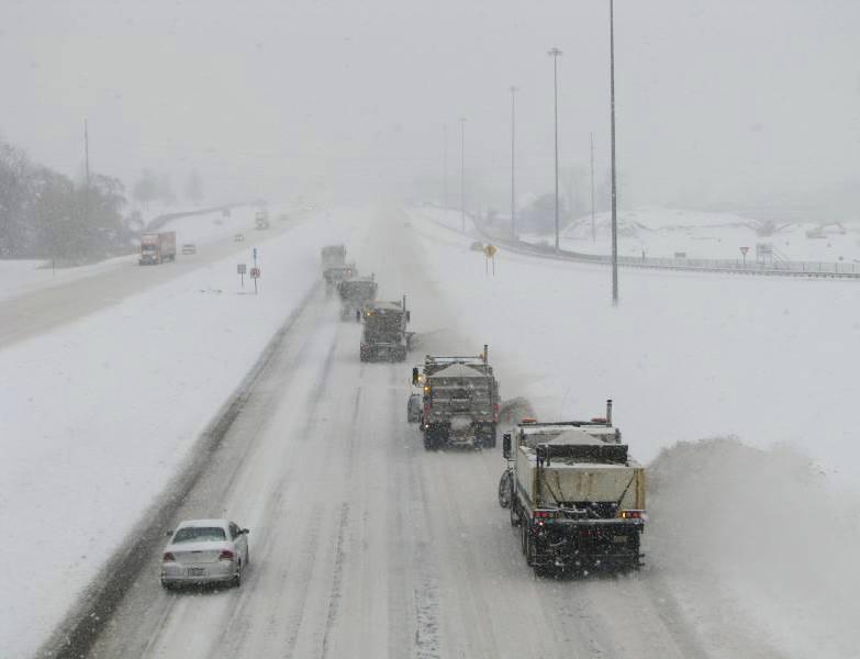 several salt trucks plow snowy road