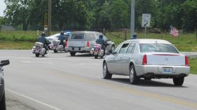 A police motorcade along Highway 31-E escorts Ellis' casket to the cemetery.