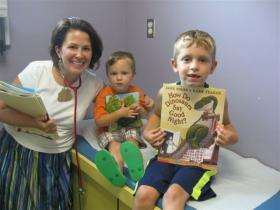 Noah Newman, 5 and brother Brady, 3 get new books from Dr. Billie Galyen at the Community Health Center in Muhlenberg County.
