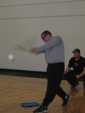 A blindfolded Fort Knox soldier takes a swing at the ball during a game of Beep Baseball.