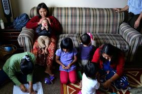 Cing Lam Nuampi comforts her nephew, Tau Sian Tuang, while surrounded by relatives spending time at her home in Owensboro, Ky.