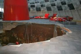 Workers want to stabilize the red spire in the center of the Skydome before removing of the Corvettes that fell into the sinkhole.