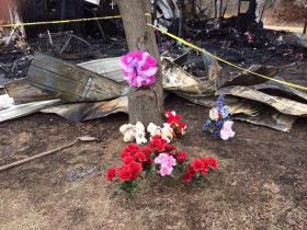 Flowers are left outside the Watson home that demolished by fire.