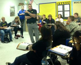 Kentucky State Police Trooper Jonathan Biven gives a safe driving presentation to students at Warren East High School.