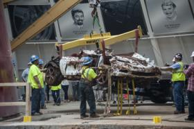 A crane lifts what's left of the 2009 1.5 Millionth Corvette from the sinkhole Thursday morning.
