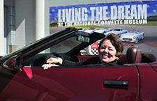 Lynda Patterson sits in her 40th Anniversary ruby red Corvette.