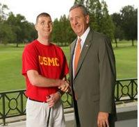 "Gen. Tommy Franks congratulates Cpl. Michael Jernigan, the recipient of the first ""Paws for Patriots\"" dog."