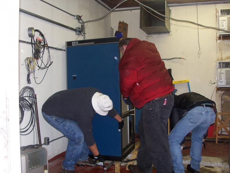 The engineering team preparing the High Voltage cabinet to be removed.  This cabinet weighs over 1600 lbs.  The corners of the cabinet are lifted and small pipes are placed underneath to roll the unit toward the door.