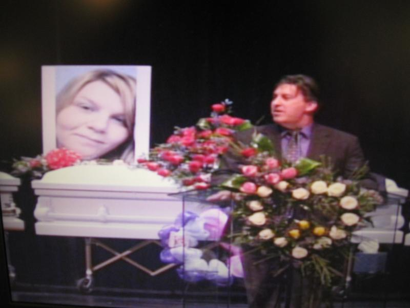 Pastor Tim Burden speaks in front of the casket of Larae Watson.