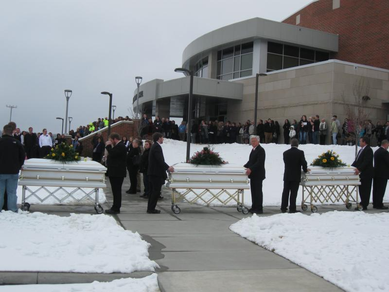 Pallbearers carry the nine caskets following the funeral service.