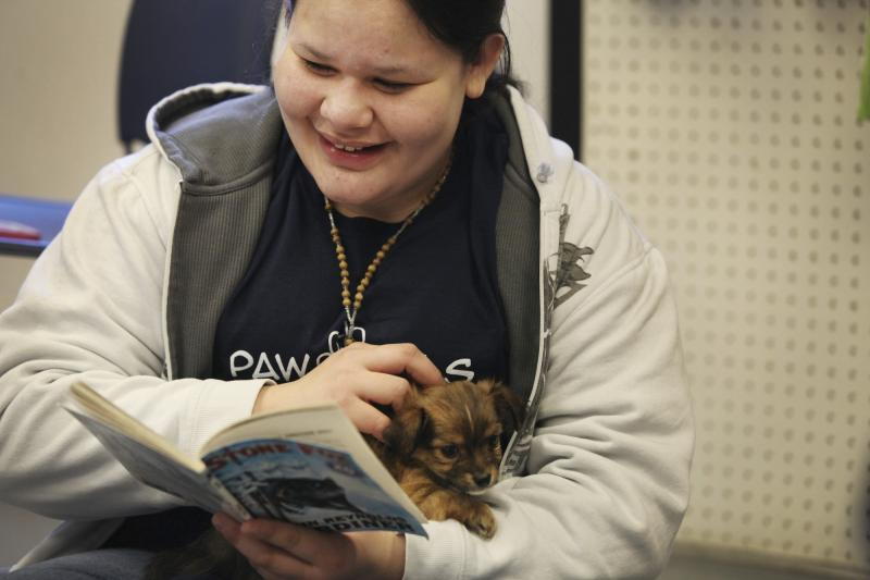 Graciella Ventura, originally from El Salvador, reads to a puppy at the Warren County Humane Society on Wednesday, April 16, 2014.