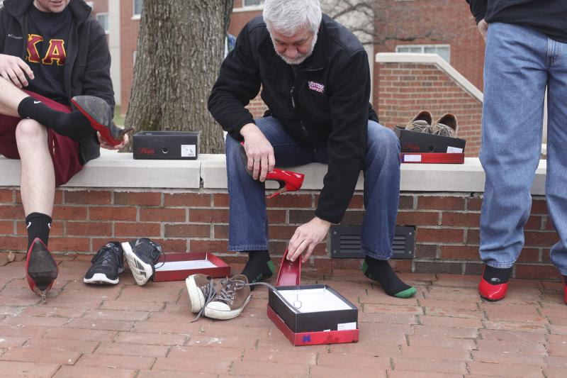 Men trade out their sneakers for red high heels before walking a mile around WKU's campus on Tuesday, March 18, 2014.