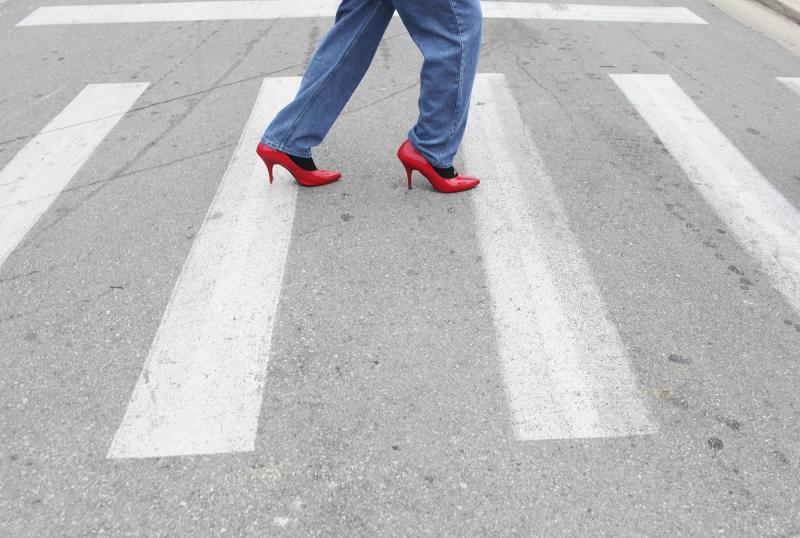 A male college student walks up the hill wearing high heels as part of Walk a Mile in Her Shoes on Tuesday, March 18, 2014.