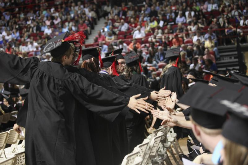 WKU students high-five each other before walking across the red carpet to receive their diploma placeholder at Diddle Arena on Saturday, May 17, 2014.
