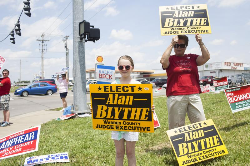 Pat Devlin of Bowling Green and her granddaughter, Anniston Goolesby, 9, of Rockfield hold campaign signs for Alan Blythe, Devlin's coworker, at the corner of Scottsville Road and Lover's Lane on Tuesday, May 20, 2014.