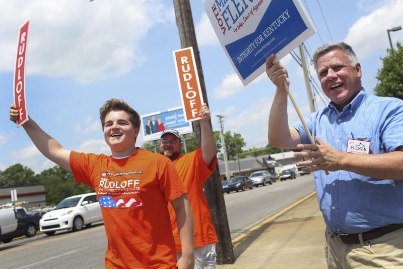 Noah Rudloff (left), Joshua Hale, and Mark Flener, all of Bowling Green, hold campaign signs at the corner of Scottsville Road and Nashville Road on Tuesday, May 20, 2014. Rudloff is the son of candidate Dan Rudloff, and Mark Flener is also a candidate.