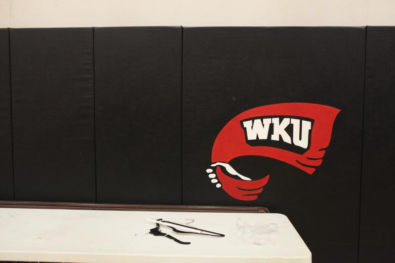 Clothing hangers sit under a WKU red towel logo in the auxiliary gym at Diddle Arena before commencement on Saturday, May 17, 2014.