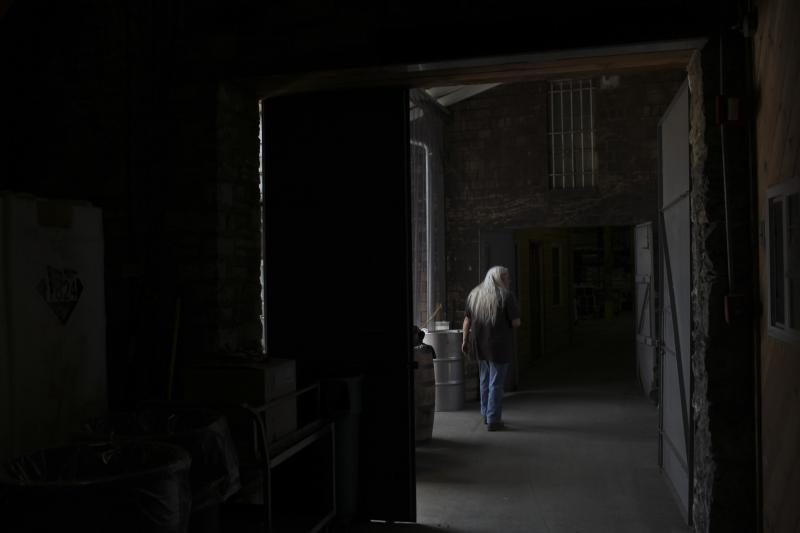 An employee walks between buildings at the Woodford Reserve Distillery in Versailles, Ky on Wednesday, April 9, 2014.
