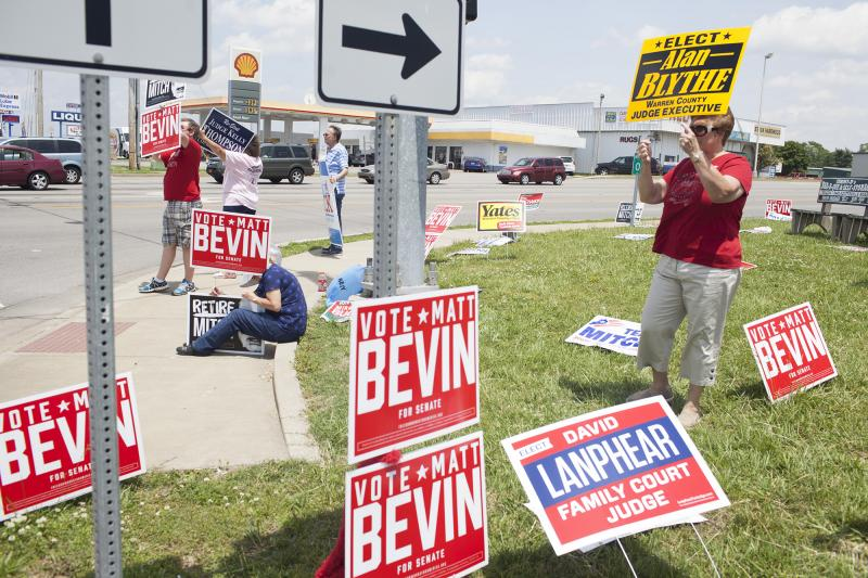 Candidates, friends and family hold signs at the corner of Scottsville Road and Lovers Lane in Bowling Green on Tuesday, May 20, 2014.