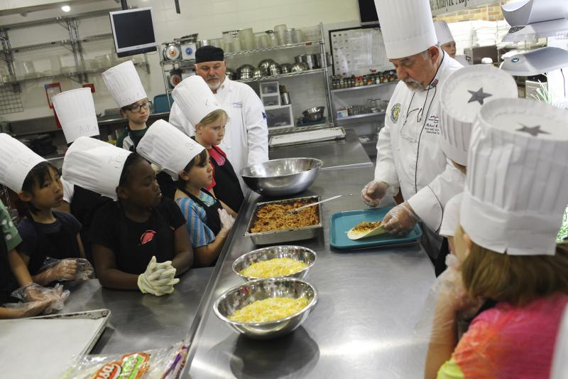 Chef Mike Riggs shows campers how to prepare quesadillas during Chef Camp at Southcentral Kentucky Community and Technical College in Bowling Green on Friday, June 13, 2014.