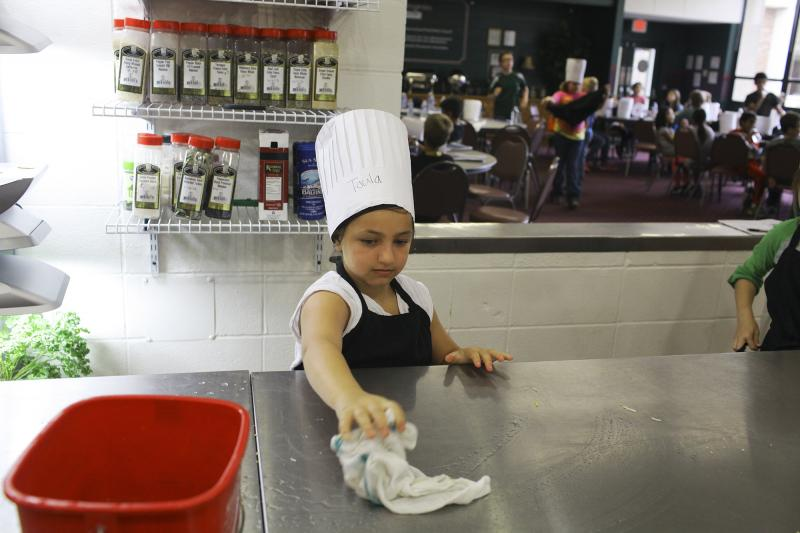 Toula Burdette, 9, of Bowling Green, cleans the counter during Chef Camp at Southcentral Kentucky Community and Technical College in Bowling Green on Friday, June 13, 2014.