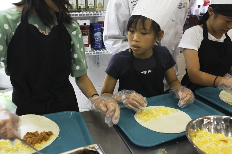 Aoi Madarame, 10, prepares a quesadilla during Chef Camp at Southcentral Kentucky Community and Technical College in Bowling Green on Friday, June 13, 2014.