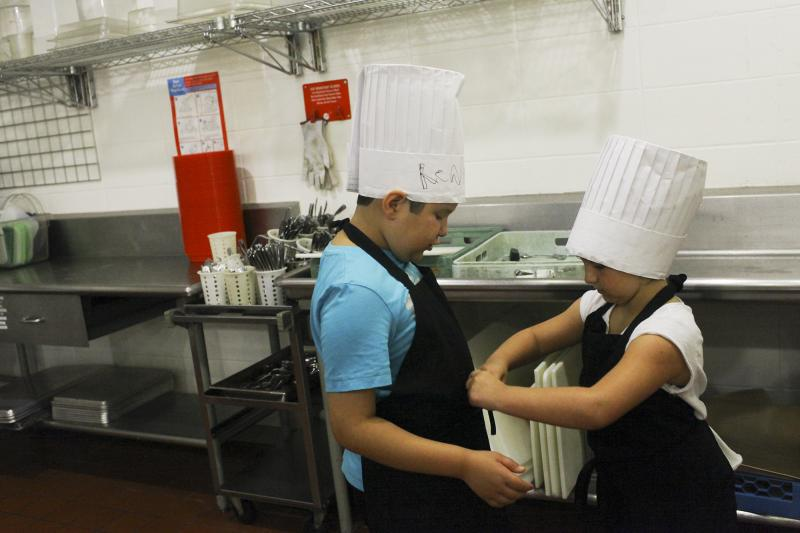 Toula Burdette, 9, of Bowling Green, helps Renaldo Teitira, 8, of Bowling Green, tie his apron during Chef Camp at Southcentral Kentucky Community and Technical College in Bowling Green on Friday, June 13, 2014.