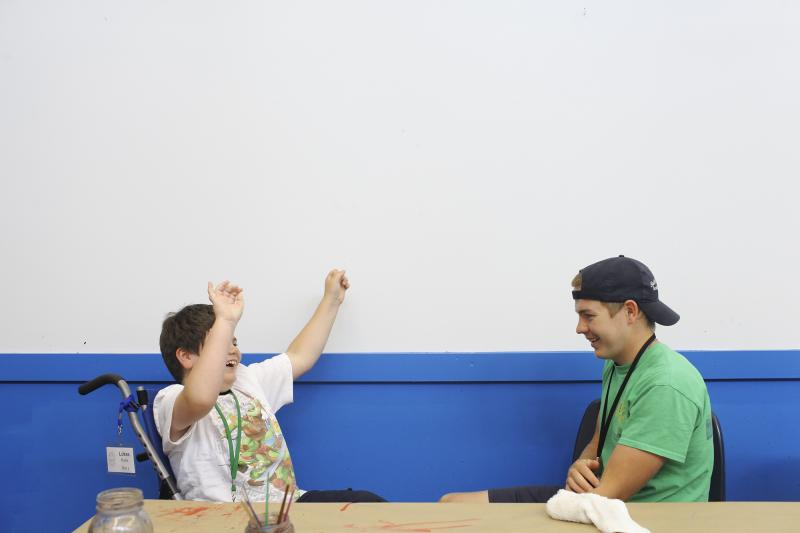 A camper and a counselor play a game in the arts building at the Center for Courageous Kids in Scottsville, Ky on Wednesday, July 2, 2014.