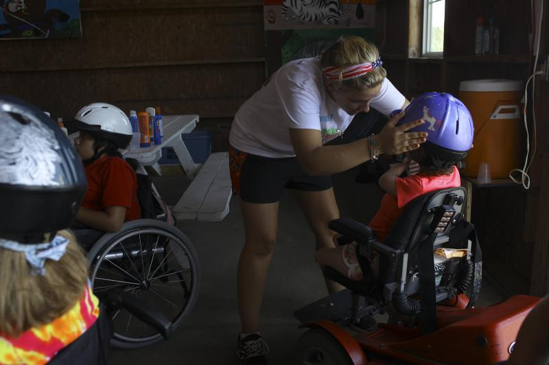 A counselor puts a helmet on a camper in the horse stable at the Center for Courageous Kids in Scottsville, Ky on Wednesday, July 2, 2014.
