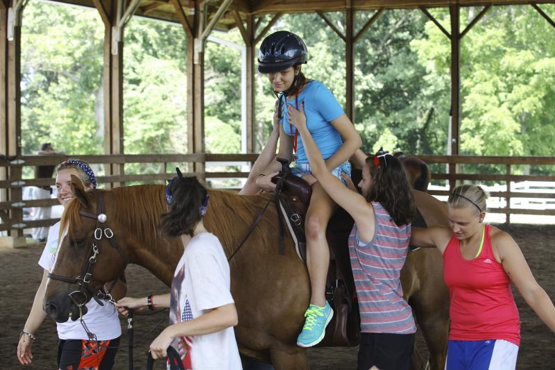 Counselors hold a camper up on a horse while she rides around the stable at the Center for Courageous Kids in Scottsville, Ky on Wednesday, July 2, 2014.