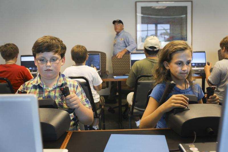 Parker Rhodes (left), 10 of Bowling Green, and Olvia Forshee, 10 of Franklin, use flight simulators at Aviation Camp at the Bowling Green Regional Airport on Tuesday, July 8, 2014.