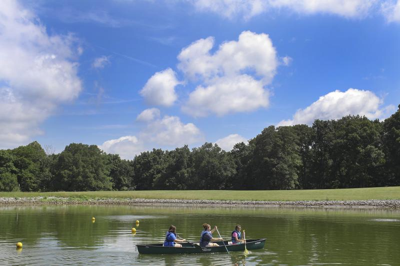 Two campers and one counselor take a canoe out on the lake at the Center for Courageous Kids in Scottsville, Ky on Wednesday, July 2, 2014.