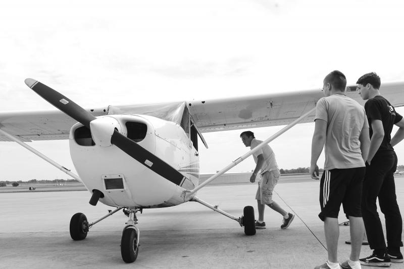 A flight instructor leads campers to the plane they will be flying at Aviation Camp at the Bowling Green Regional Airport on Tuesday, July 8, 2014.