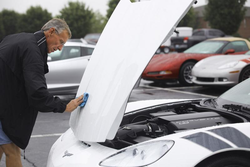 Jeff Snapp of Corbin, KY dries off his Corvette outside the Sloan Convention Center in Bowling Green on Saturday, July 19. Snapp's wife, Patty, says whenever they take their Corvette out, it always seems to rain.