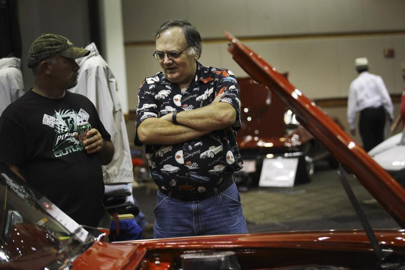 Dennis Byrd of Bellaire, MI, right, talks to a fellow Corvette enthusiast about the red Corvette he restored