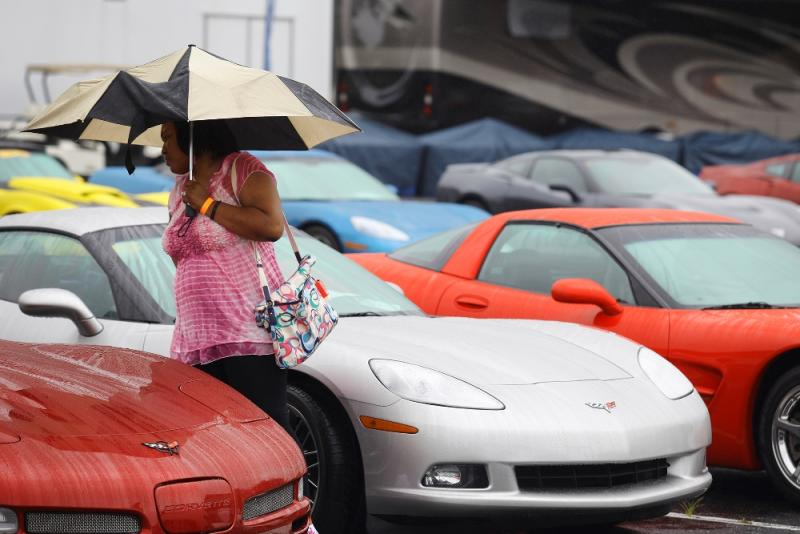 A Corvette Homecoming visitor braves the rainy weather to check out the Corvettes during the Corvette Homecoming outside the Sloan Convention Center in Bowling Green on Saturday, July 19
