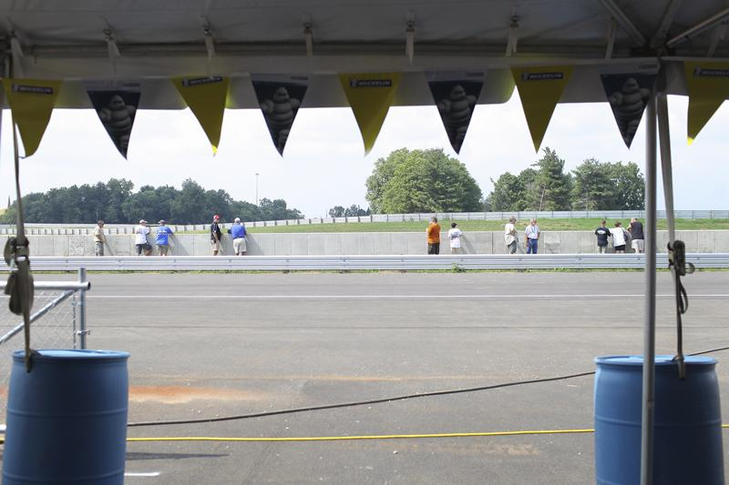 People watch as Corvette owners drive their cars around the new track at the National Corvette Museum Motorsports Park Thursday, August 28, 2014. The track opened Thursday morning.