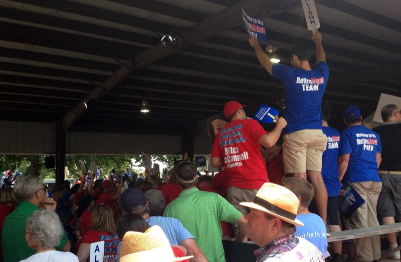 Supporters of both U.S. Senate candidates hold up signs at Fancy Farm 2014