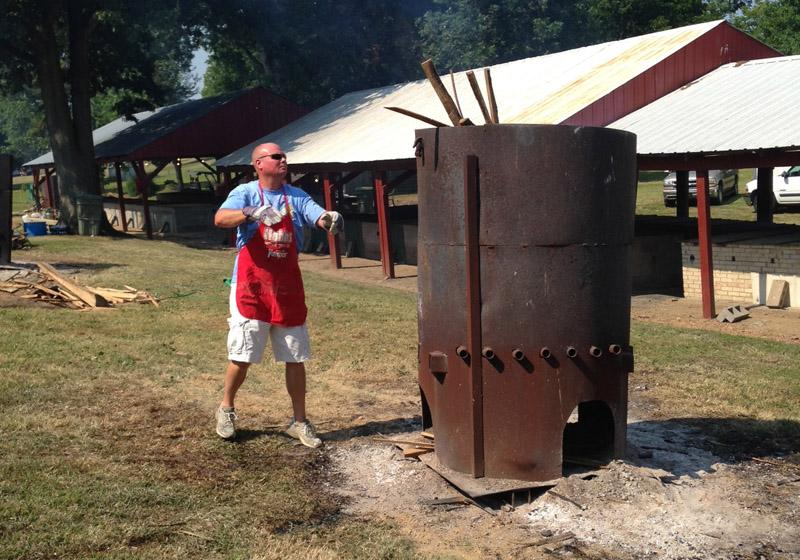A volunteer adds firewood. BBQ pork and mutton are big parts of Fancy Farm along with hot dogs and burgers