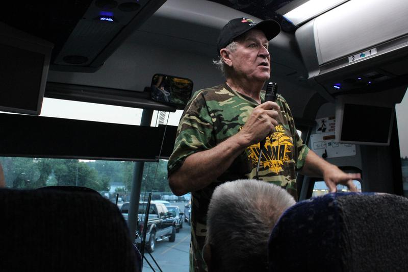 Retired miner and union leader Joe Holland speaks to a bus full of retirees and spouses.