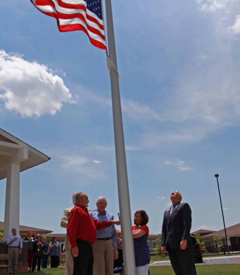 Paul Craigmyle, left, in red shirt, and Eugene Hill, in blue shirt, the first two residents of the Radcliff Veterans Center, raise the flag. At right is Commissioner Norman Arflack of the Kentucky Dept. of Veterans Affairs.