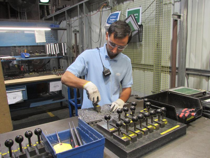 Mohammad Jawid, who is from Afghanistan and speaks five languages, works on quality control of the precision automotive parts.