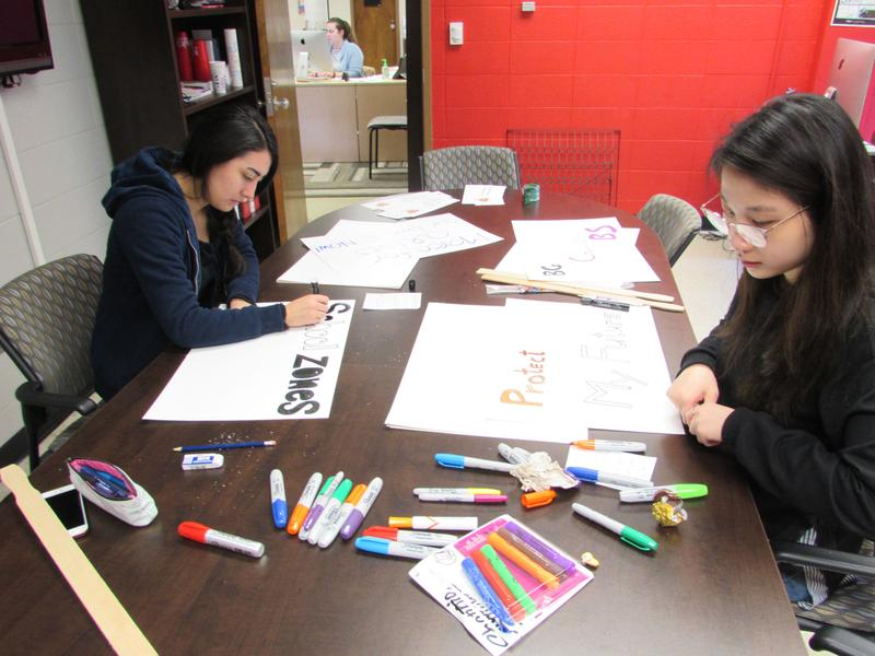 Milagros Pazmino, left, and Nga Nguyen create posters for the Bowling Green 'March for Our Lives' on Saturday.