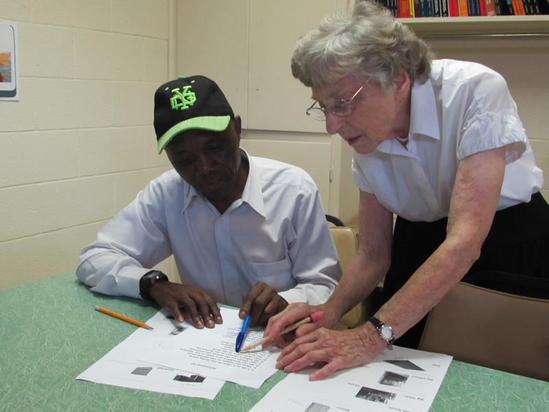 Working on an English language lesson are, left, Kilozo Lubwena, who is fluent in Bembe and Swahili and proficient in French, and Kentucky Refugee Ministres volunteer Dorothy Sinatra, who is retired from her career as a draftsperson.