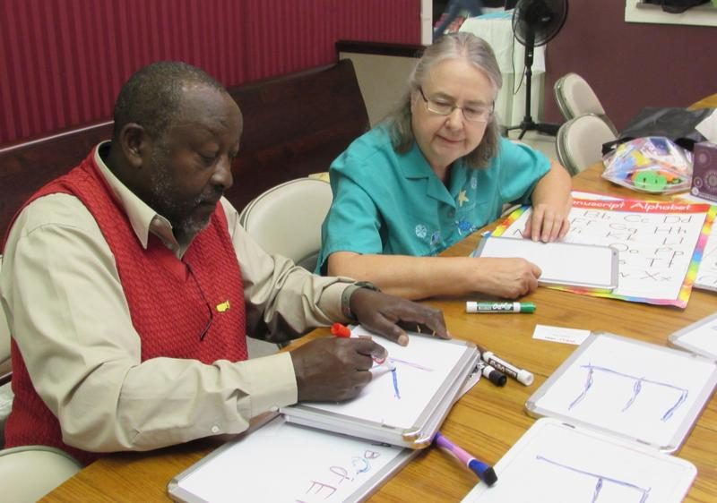 Ramadhan Munyarugero, left, and Catholic Charities volunteer English instructor Bonnie Lossie work on a language lesson at the Refugee Elder Program in Louisville, Kentucky.