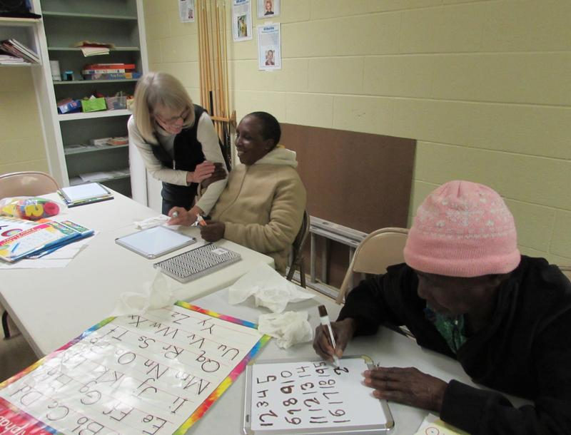 Volunteer English teacher Kevin Marie Nuss reviews letters and numbers with Namagishu Namahoro, center, and Kwirina Ngeze.