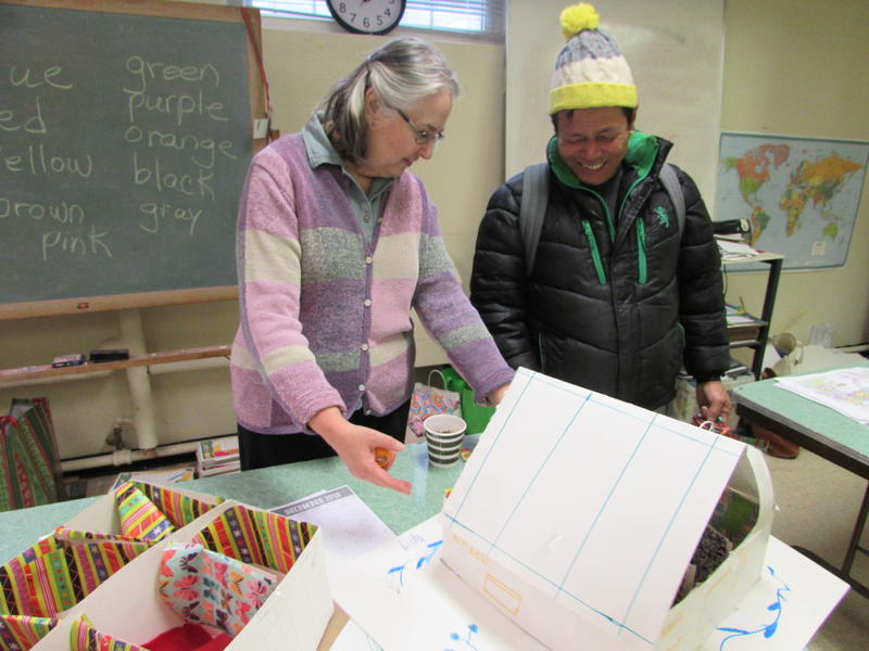 Volunteer English teacher Bonnie Lossie looks over an art project with Aita Signh-Gurung, who is from Bhutan and created a house common in his home country.
