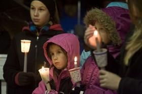 From left, sisters Sara, 12, Jessica, 6, and Kaitlyn Gerckens, 10, gather Sunday night during a vigil to remember the lives lost during Friday's shooting at Newtown's Sandy Hook Elementary School.