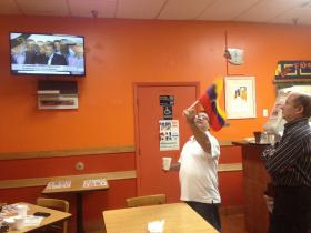 Cafe Canela owner Ramon Peraza waves a Venezuelan flag during a news report on the death of Hugo Chavez.