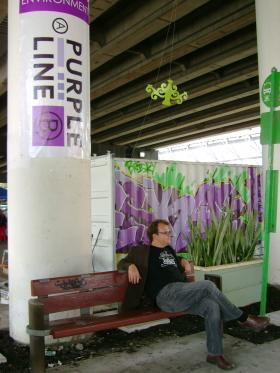 The director of Florida Atlantic University's school of urban and regional planning, Eric Dumbaugh, relaxes at the bus stop next to the Purple Line. FAU was one of the organizations that sponsored the event.